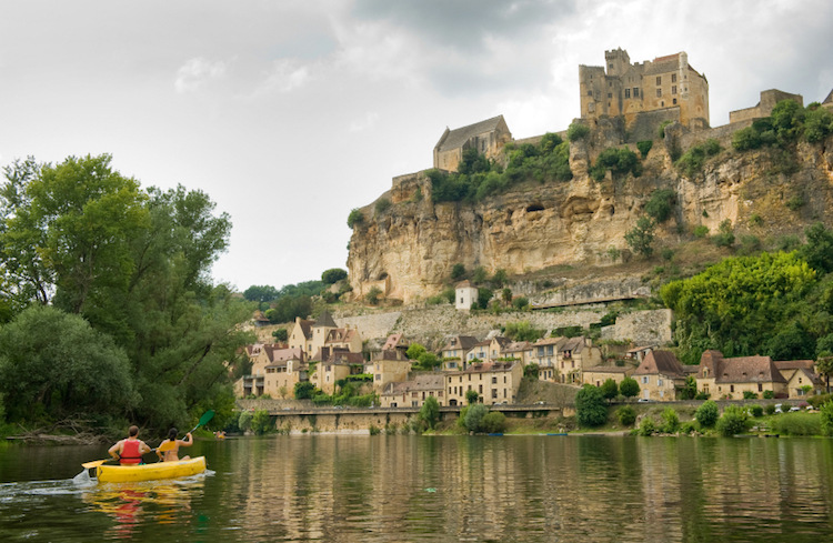 A canoe floats past the fortified town of Beynac-et-Cazenac, Dordogne. Photo: iStock