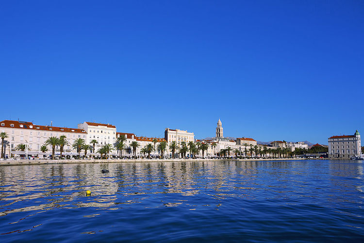 Croatia, Split, Houses and palm trees behind blue sea. (Photo by: JTB/UIG via Getty Images) (Photo by: JTB Photo/UIG via Getty Images)