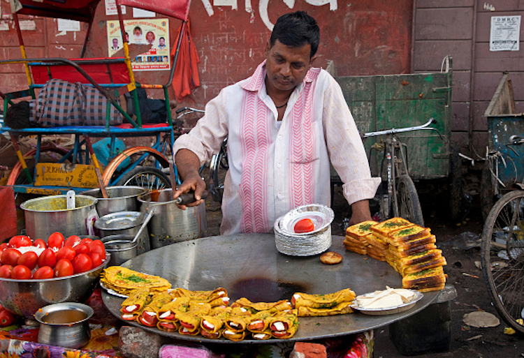 Man cooking food on the street in Old Delhi, India. (Photo by: Arterra/UIG via Getty Images)