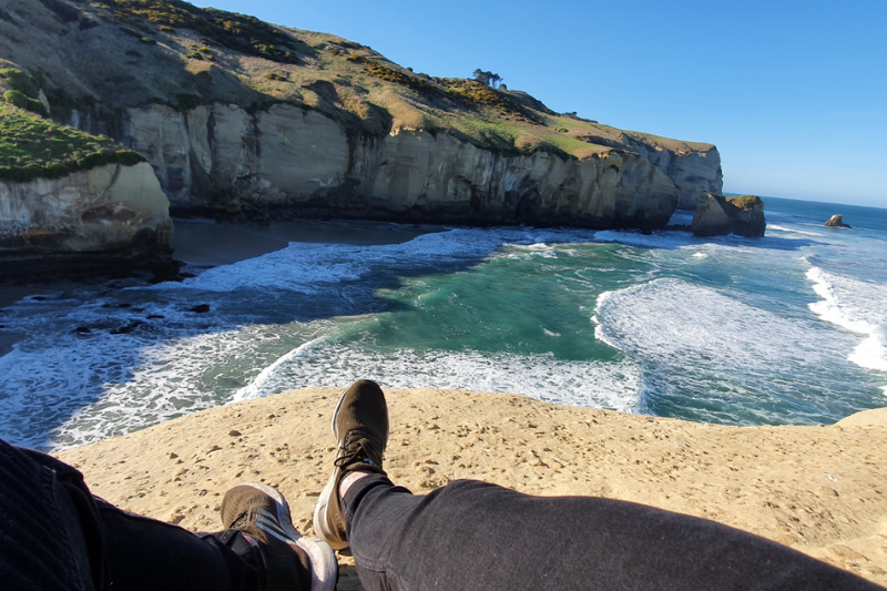 On top of the natural sandstone bridge over the ocean at Tunnel Beach